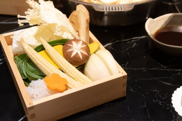 신선한 음식은 나무 정사각형 상자에 버섯, 야채 및 국수로 구성