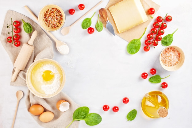Свежие пищевые ингредиенты и кухонные принадлежности для приготовления пиццы или соленого пирога.