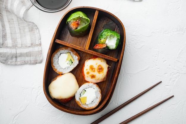 寿司ロールがセットされた日本の弁当箱の生鮮食品部分、白い石の背景、上面図フラットレイ、コピースペースとテキスト用のスペース