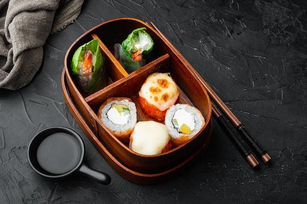 Fresh food portion in japanese bento box with sushi rolls set, on black stone