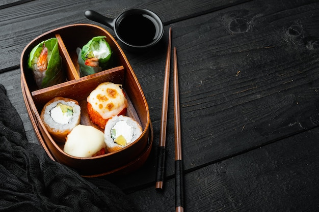 Fresh food portion in japanese bento box with sushi rolls set, on black wooden table