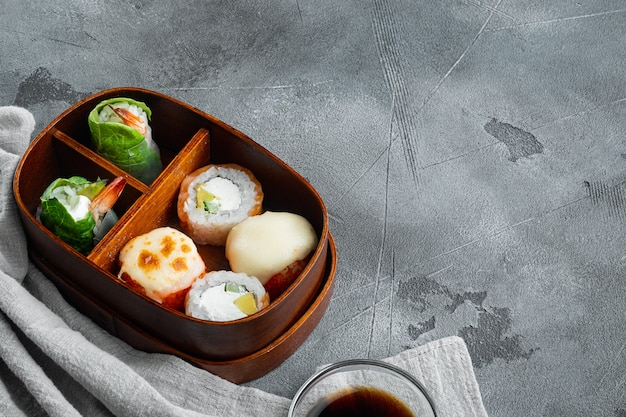 Fresh food portion in japanese bento box with sushi rolls set, on gray stone