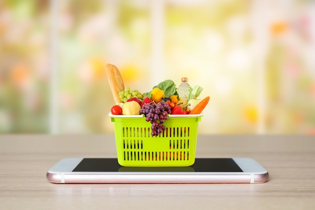 Fresh food and vegetables in green shopping basket on mobile smartphone on wood table with window and garden abstract blur background grocery online concept