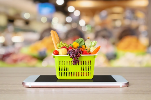Fresh food and vegetables in shopping basket on mobile smartphone on wood table with supermarket aisle blurred background grocery online concept