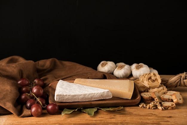 Свежие продукты с чесноком, сыром и виноградом возле коричневой ткани на столе