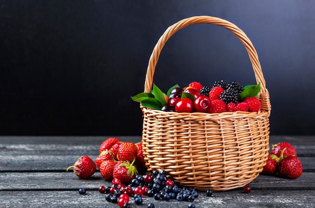 Fresh forest berries in basket on dark