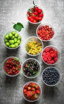 Свежие лесные ягоды в очках. на каменном столе.