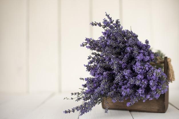 白の木製バスケットにラベンダーの新鮮な香りの花束。