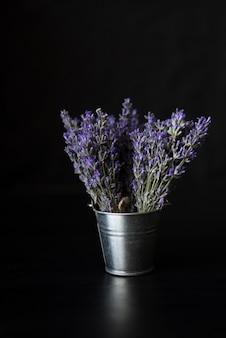 黒のバケツに新鮮な香りのラベンダーの花束。プロヴァンスのハーブ。ラベンダーの心地よい心地よい香り。