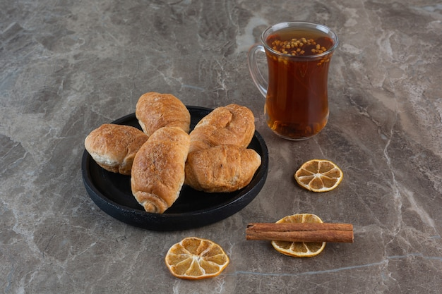 Fresh fragrant tea with homemade cookies on grey.