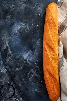 灰色の古いコンクリートの新鮮なフランスのバゲットパン。テーブル