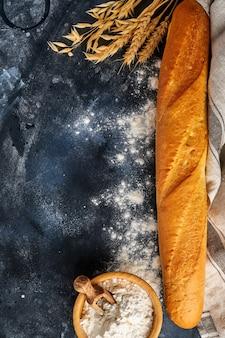 灰色の古いコンクリートのテーブルに新鮮なフランスのバゲットパン、小麦粉、耳