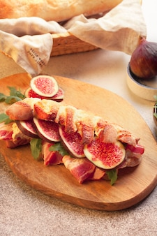 Fresh french baguette with cream cheese, figs, bacon and arugula