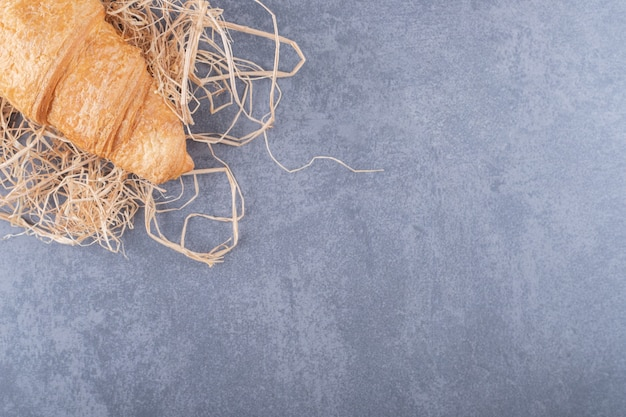 Fresh french croissant on straw over grey background.
