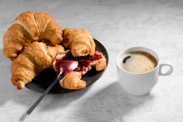 Fresh french croissant with cherry jam on grey plate and cau of fresh coffee on gray background, one teaspoon spreads jam on croissant, delicious sweet breakfast with pastries