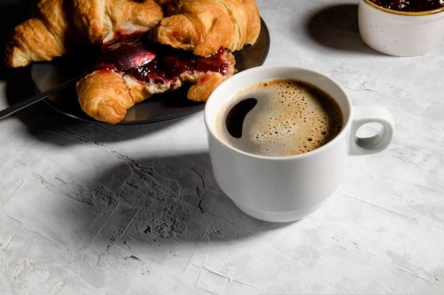 グレーのプレートと淹れたてのコーヒーのキャップにチェリージャムを添えたフレッシュフレンチクロワッサン