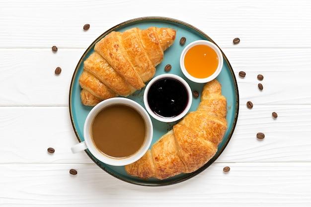 ブルーベリージャム、蜂蜜、一杯のコーヒーと新鮮なフレンチクロワッサン