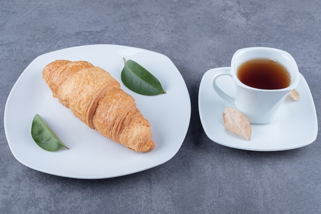 Croissant francesi freschi con una crosta dorata con una tazza di tè.