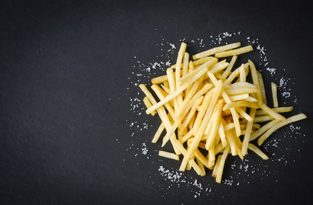 Fresh french fries with salt on black plate , top view copy space - tasty potato fries for food or snack delicious italian meny homemade ingredients