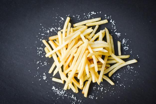 Свежий картофель фри с солью на черной тарелке