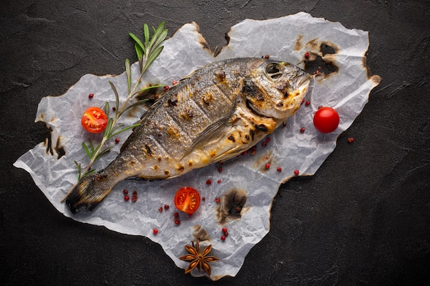 Fresh fried dorado fish with spices on black background