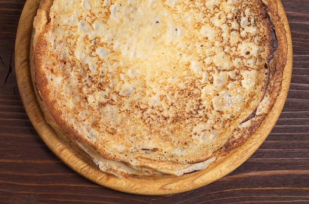 木製のテーブルの上の焼きたての揚げパンケーキをクローズアップ、上面図