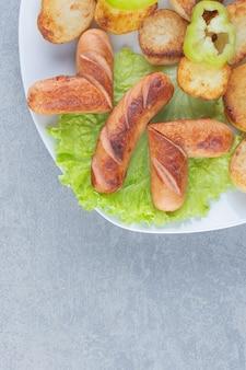Свежий жареный картофель и колбаса на белой тарелке.