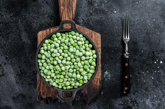 鍋に新鮮な冷凍グリーンピース。黒の背景。上面図。
