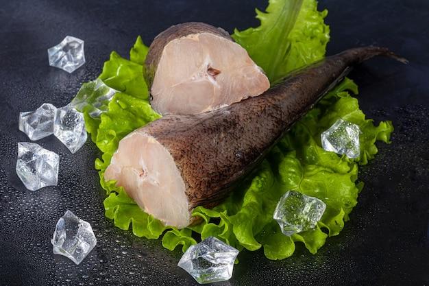 Туша хека свежезамороженная. филе рыбы с кулинарными ингредиентами, зеленью, перцем и лимоном на черной поверхности. копировать пространство