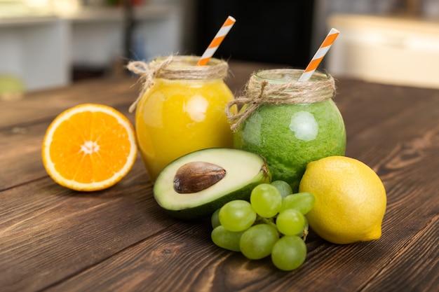 キッチンテーブルにスムージーと新鮮な果物と瓶