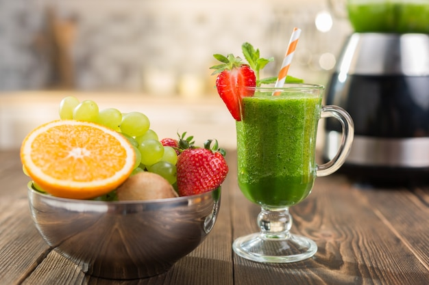 ガラスの台所のテーブルに新鮮な果物と野菜のスムージー