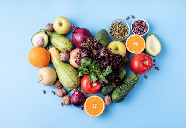 ハート形の新鮮な果物や野菜の上面図フラットは青い背景の上に横たわっていた