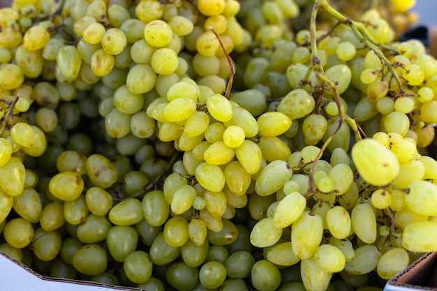 Бранч из свежих фруктов зеленый виноград в бумажных коробках на местном городском фруктовом рынке