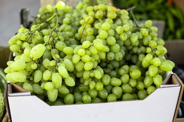 Fresh fruit brunch green grapes in paper boxes at grocery store local products