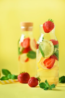 Fresh fruit flavored water with strawberry, lemon, mint on yellow background.