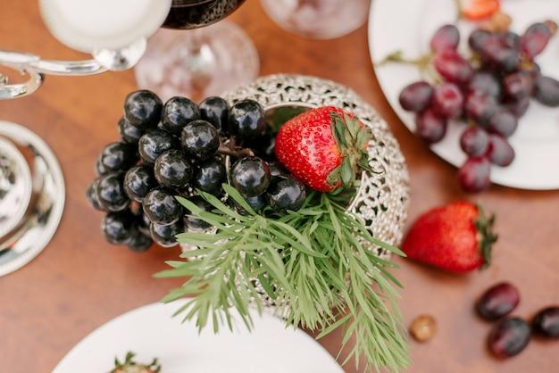 Свежие фрукты, виноград и клубника в сервировке стола или украшения