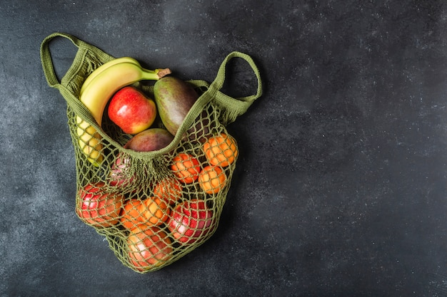 Fresh fruit in a green string bag. bananas, apples, oranges, and mangoes.