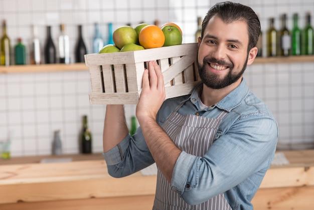 Свежие фрукты. красивый ответственный работник-энтузиаст, не уставший, выглядит не уставшим, держит тяжелую деревянную коробку со вкусными свежими фруктами и весело улыбается