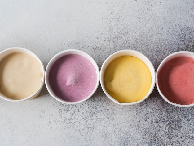 Fresh fruit ice cream of different colors in paper cups on a gray background. top view. copy space
