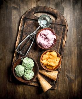 Мороженое из свежих фруктов с вафельными стаканчиками. на деревянном столе.