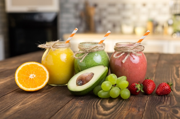 Fresh fruit and jar with smoothie on kitchen table