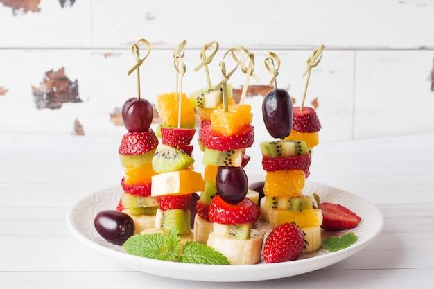 串に刺した新鮮な果物。夏のパーティーのためのコンセプトビュッフェ。コピースペース