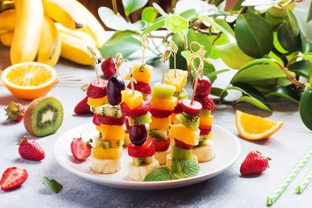 串に刺した新鮮な果物。夏のパーティーのためのコンセプトビュッフェ。
