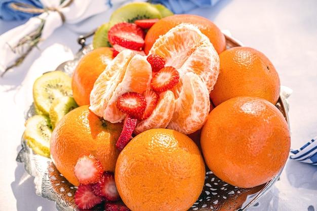 Свежие фрукты, апельсин и клубника нарезанные на пикнике
