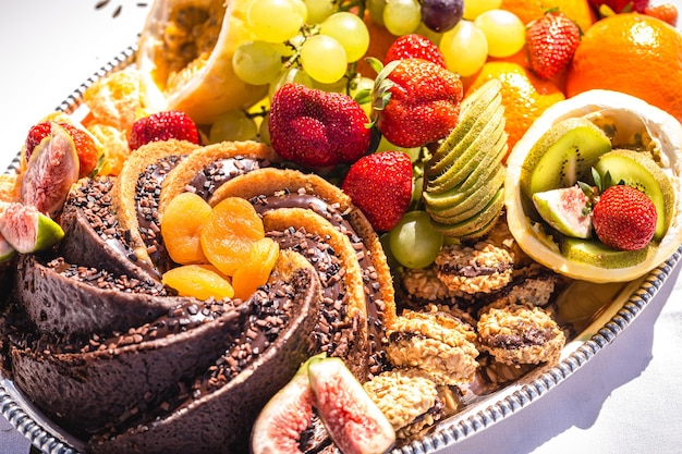 Свежие фрукты, апельсин, киви, виноград и нарезанная клубника на пикнике