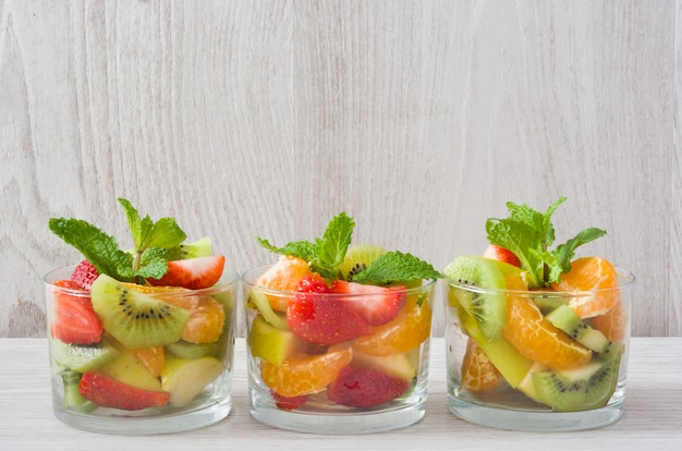 Fresh fruit salad in glass on wooden table