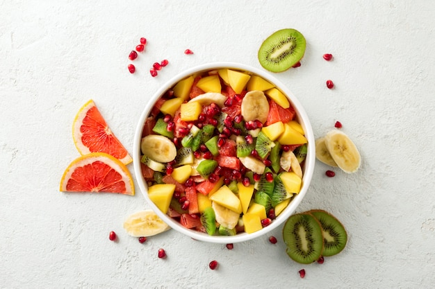 Fresh fruit salad on light surface top view summer food concept