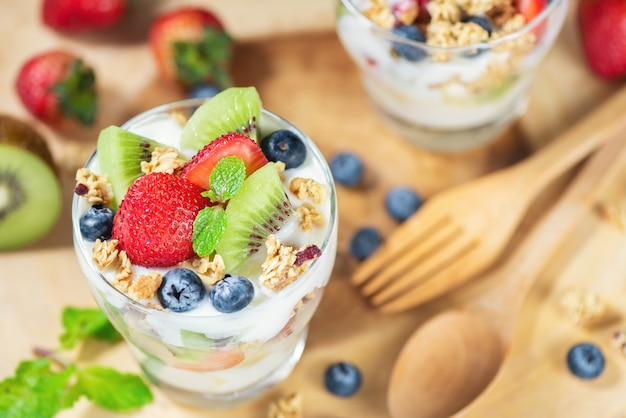 Fresh fruit salad with yogurt and berry in glass on wooden plate