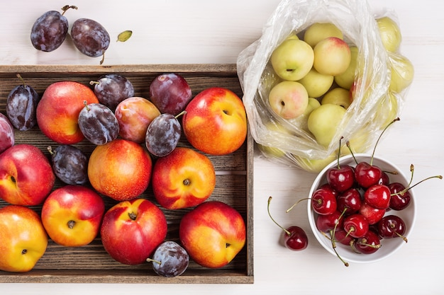 Набор свежих фруктов. сливы и нектарины в коробке, вид сверху.
