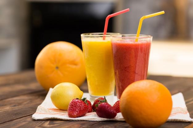 2つのガラスの台所のテーブルの上の新鮮なフルーツのスムージー
